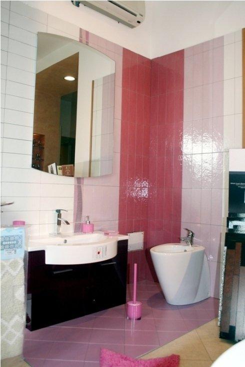 bagno con parete e pavimento rosa
