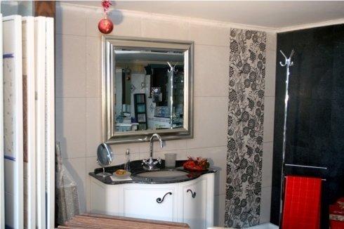 lavandino con mobile e specchio in un bagno