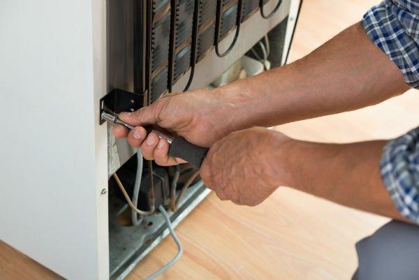 operatore riparando un frigo