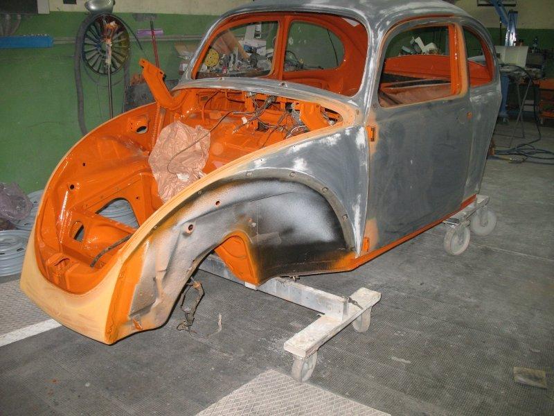 vista laterale di una carrozzeria di un maggiolino arancione e grigio