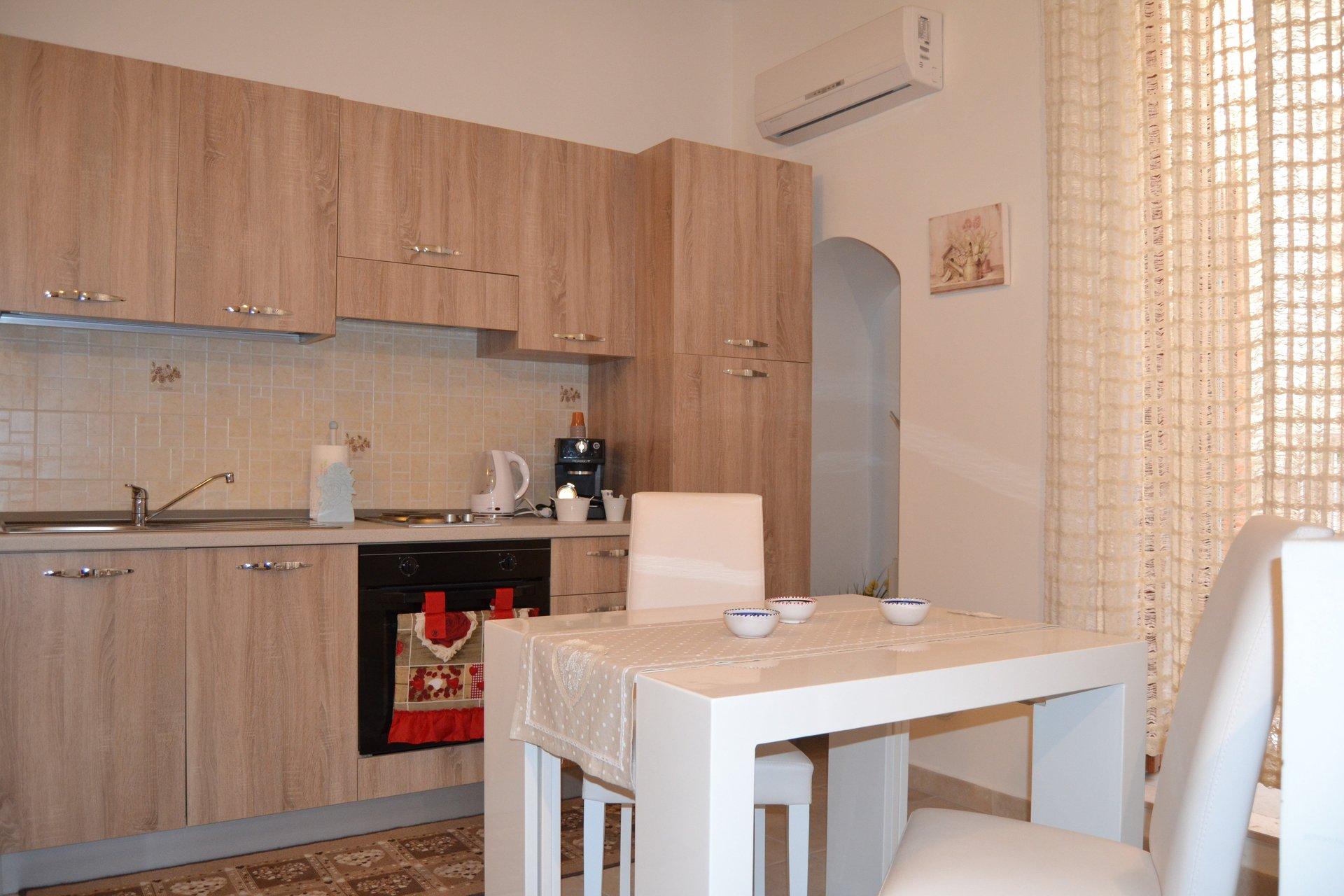 una cucina con mobili marroni e un tavolo bianco