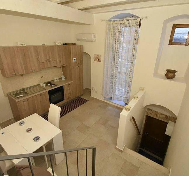 la cucina con mobili in legno e un tavolo bianco con delle sedie