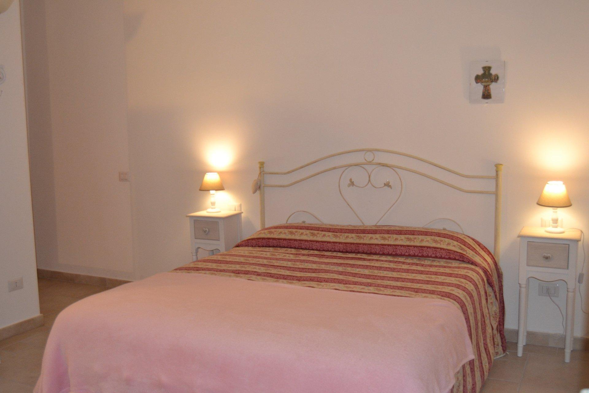un letto in ferro battuto con coperte di diversi colori