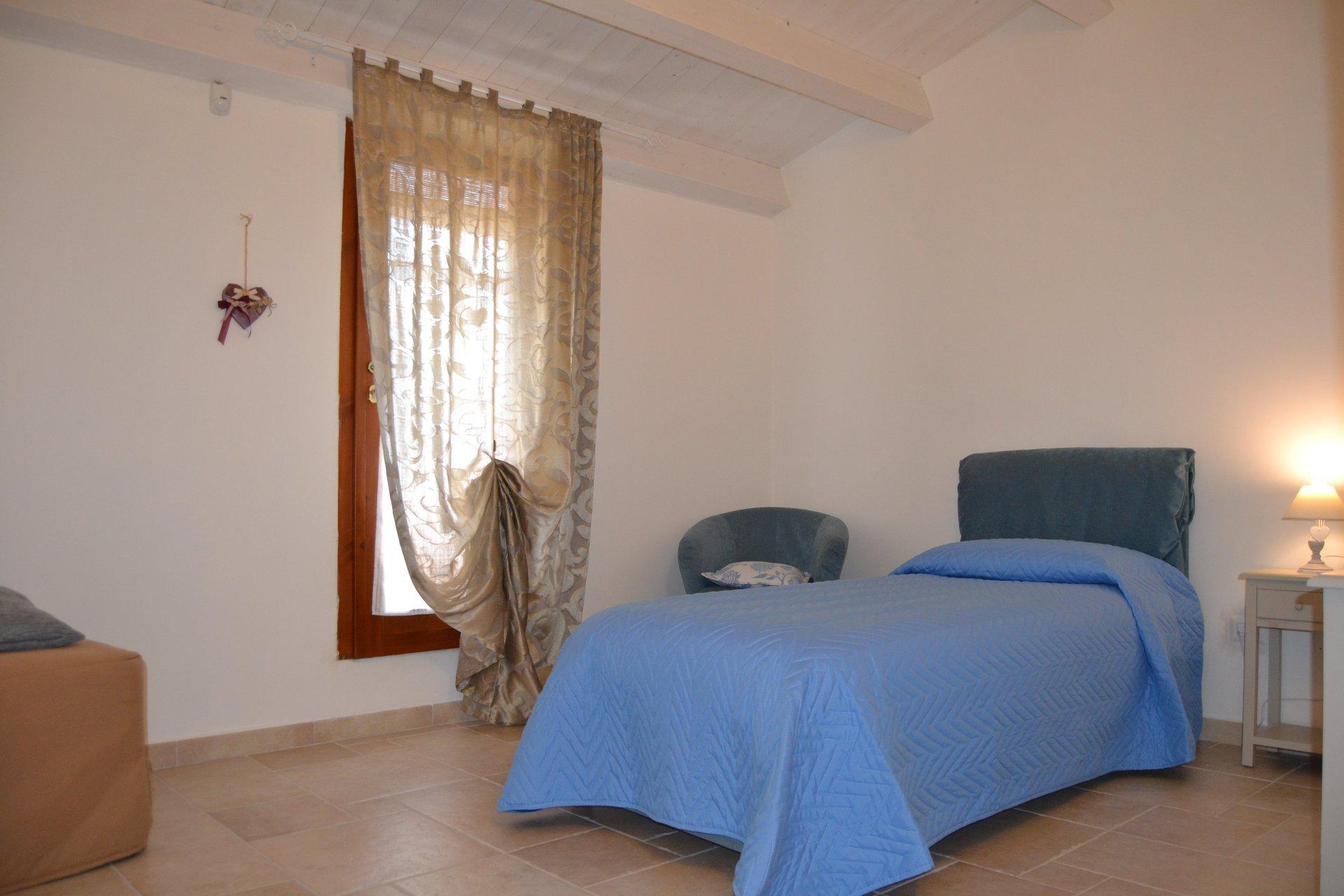 un letto con una coperta blu e delle tende alle finestre