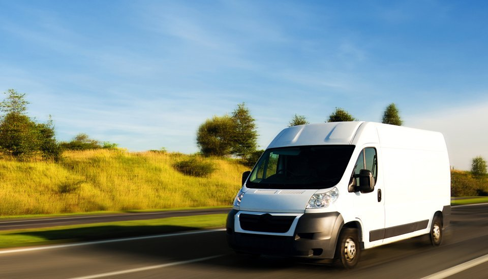 A white van travelling down a road