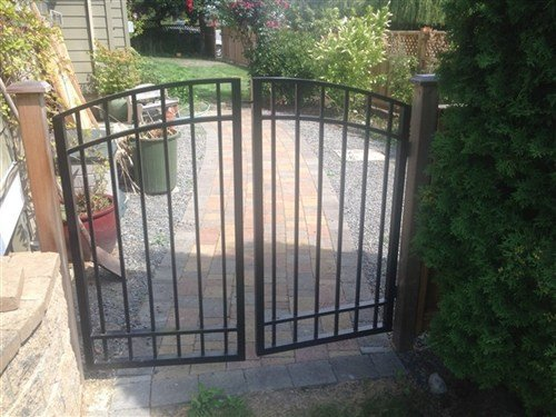 Black straight picket double gate attached to stone walkway