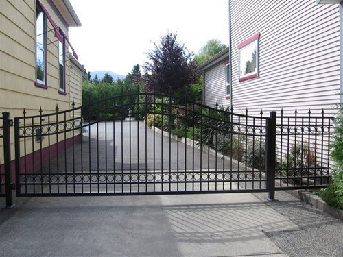 Black picket gate with spears and rings between two large houses and a black top driveway