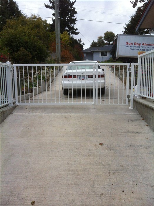 White straight picket double gate attached to concrete driveway
