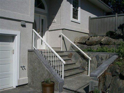 White square hand rails attached to stone stairs