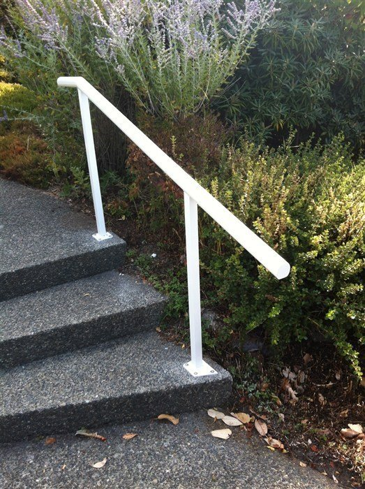 White round hand rail attached to black pebble steps