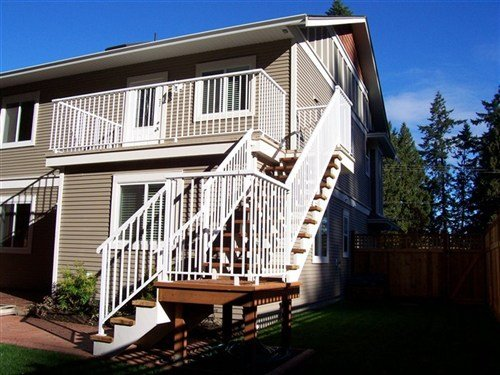 White round top aluminum railings, medium stain wooden deck attached to beige painted house with wood siding viewed from the right side