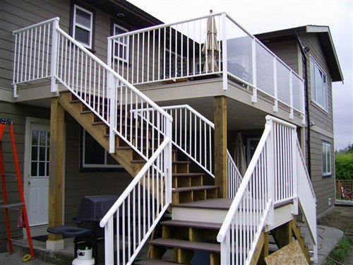 White round top aluminum railings, medium stain wooden deck attached to beige painted house with wood siding viewed from the left side
