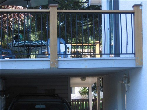 Black picket railings with wood top rails and posts attached to blue painted wood deck