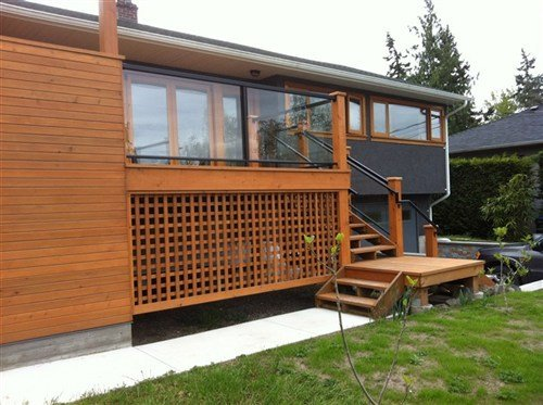 Clear tempered side mount with black square aluminum railings attached to medium stain wooden deck attached to dark grey house
