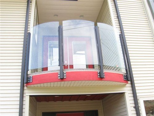 Topless aluminum glass railings with black metal posts and a red wooden deck attached to a tan siding apartment building