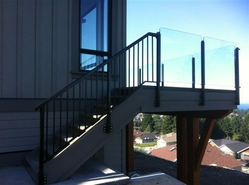Topless aluminum glass railings with black metal posts and a grey deck overlooking pine trees and houses