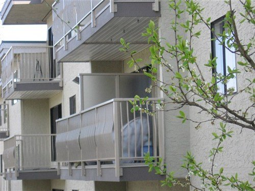 Beige basket picket square top aluminum railings attached to apartment balcony