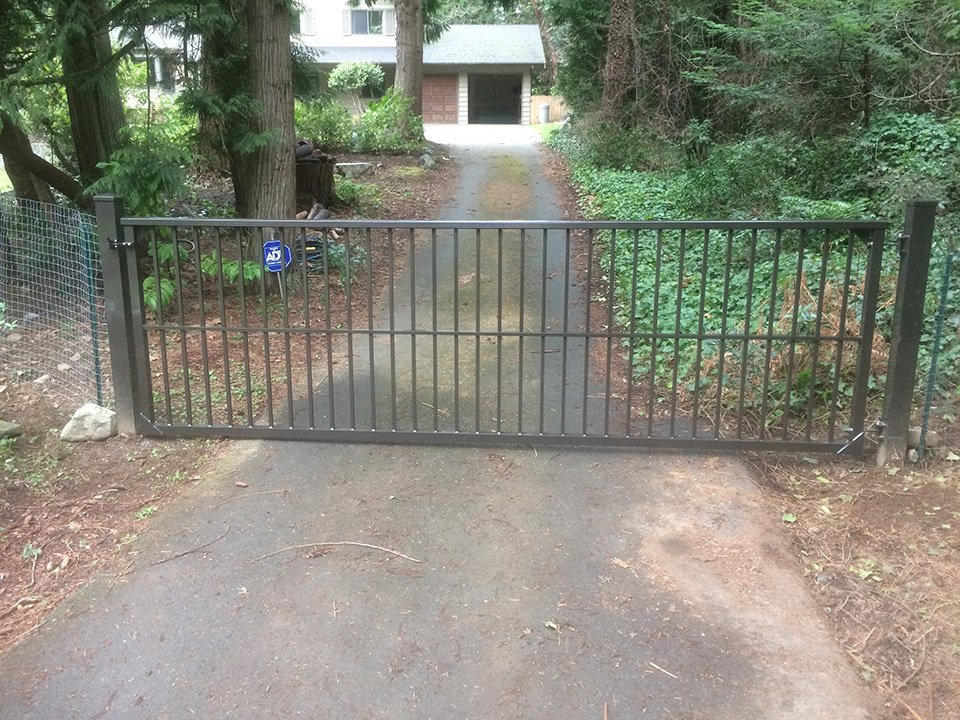Black pick gate with round square top rail profile attached to medium stain wooden fence and concrete driveway