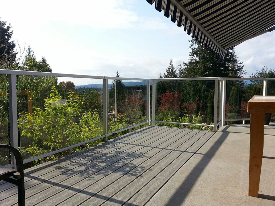 Topless aluminum glass railings attached to concrete padio with beige furniture and red and tan umbrellas overlooking pine trees and mountains