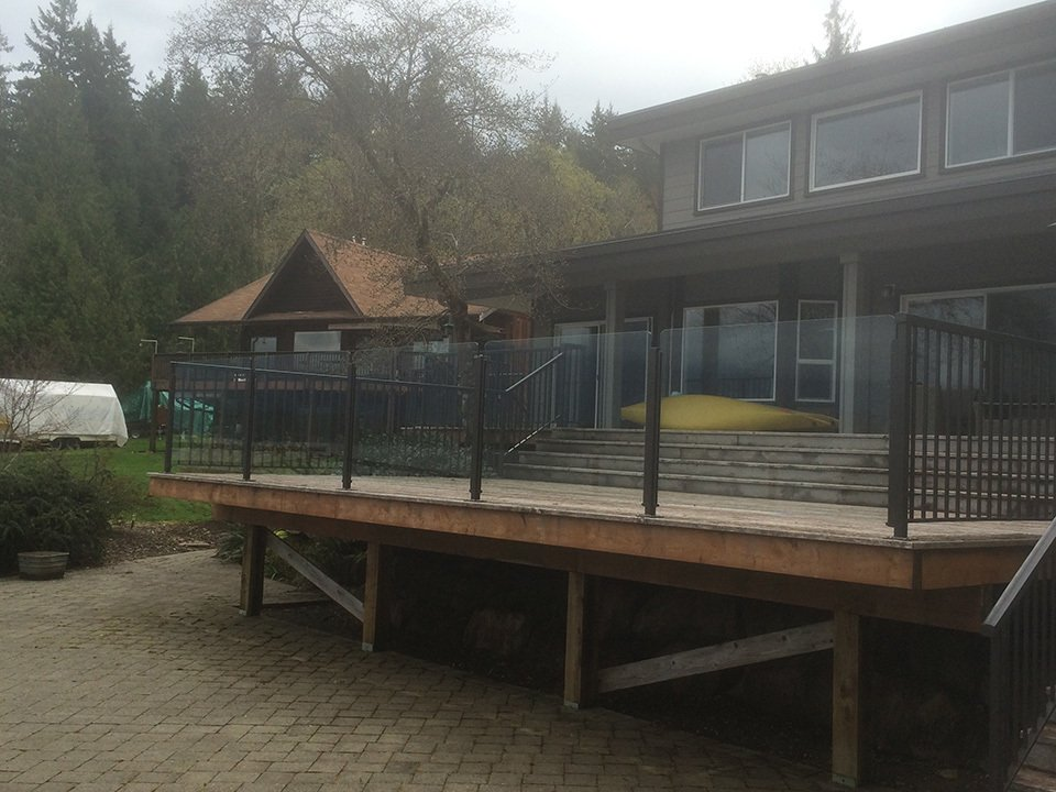 White clear tempered side mount round aluminum railings attached to natural finish wooden stairs and deck