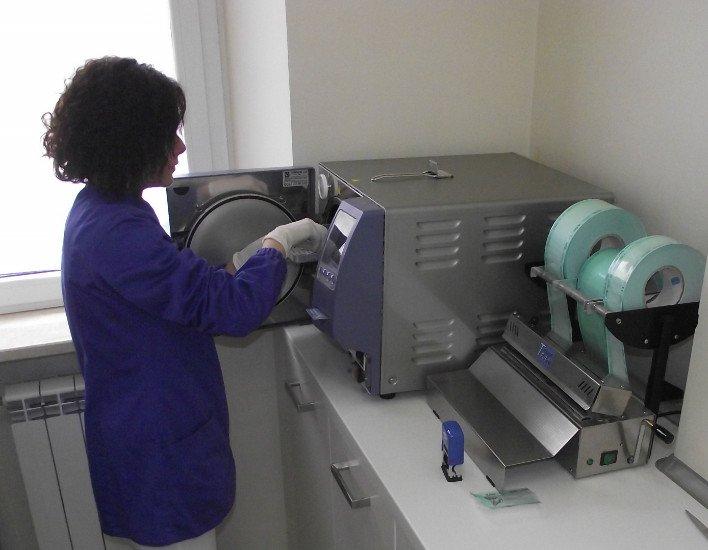 una donna che tira fuori del materiale dentistico da un apparecchiatura