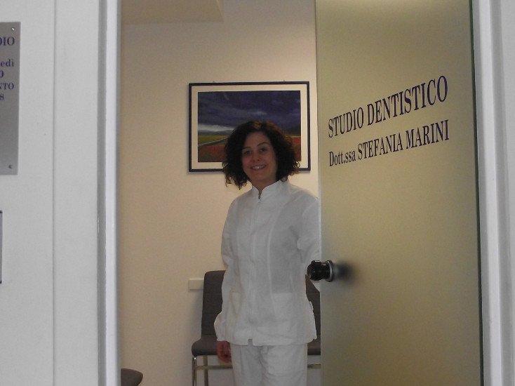 una donna con un camice vicino alla porta