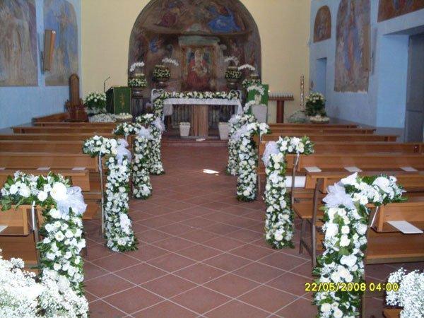 addobbi floreali sulle panche di una chiesa