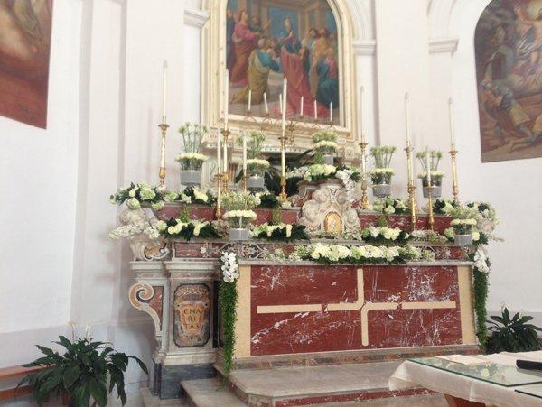 presbiterio di una chiesa con addobbi floreali