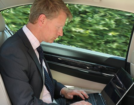 Business man on the way to airport in chauffeur driven car