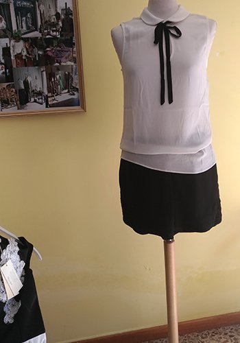 un top bianco  e una minigonna nera su un manichino