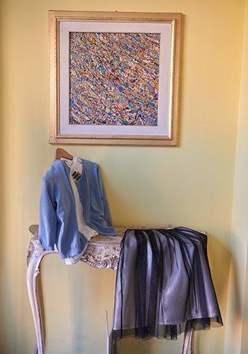 un quadro al muro e sotto una camicia azzurra e altro