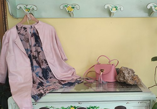 una camicia rosa e una borsa su un tavolo di vetro