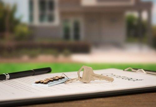 Immagine di un contratto, con penna e chiavi