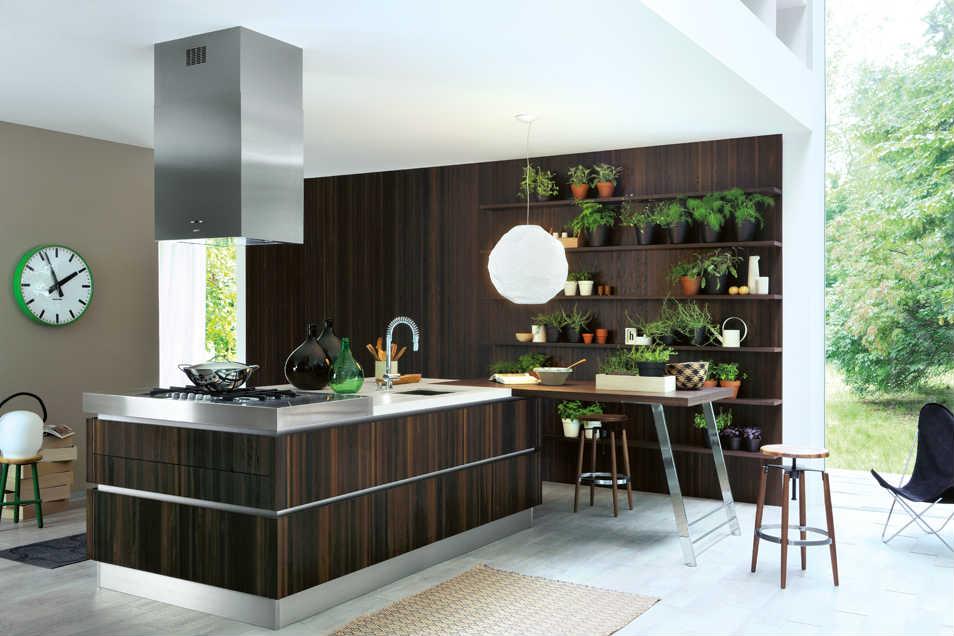 Cucina aperta con mobile centrale,estrattore di acciaio,tavolo di lavoro e scaffale alla parete piena di piante di spezie naturali