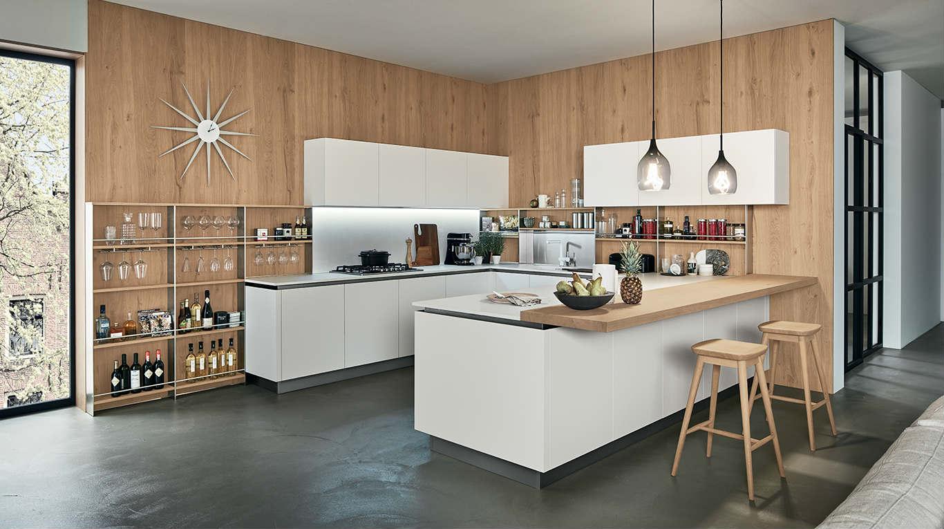 Cucina di legno,mobili bianchi,le scaffali della parete custodiscono bicchieri e bottiglie di vino