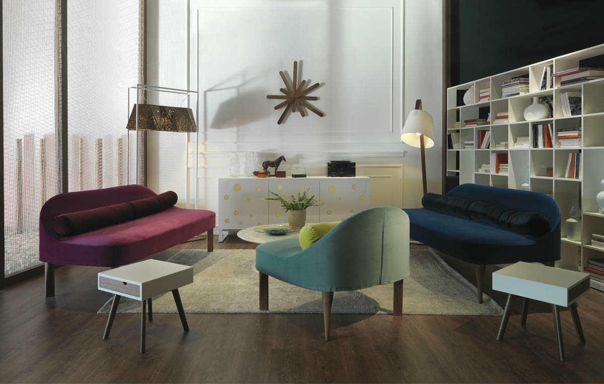 Soggiorno con poltrona verde grigio, divano blu , divano granate,originale lampadina pendaglio di biliardo,stella di legno nella parete e scaffale bianca