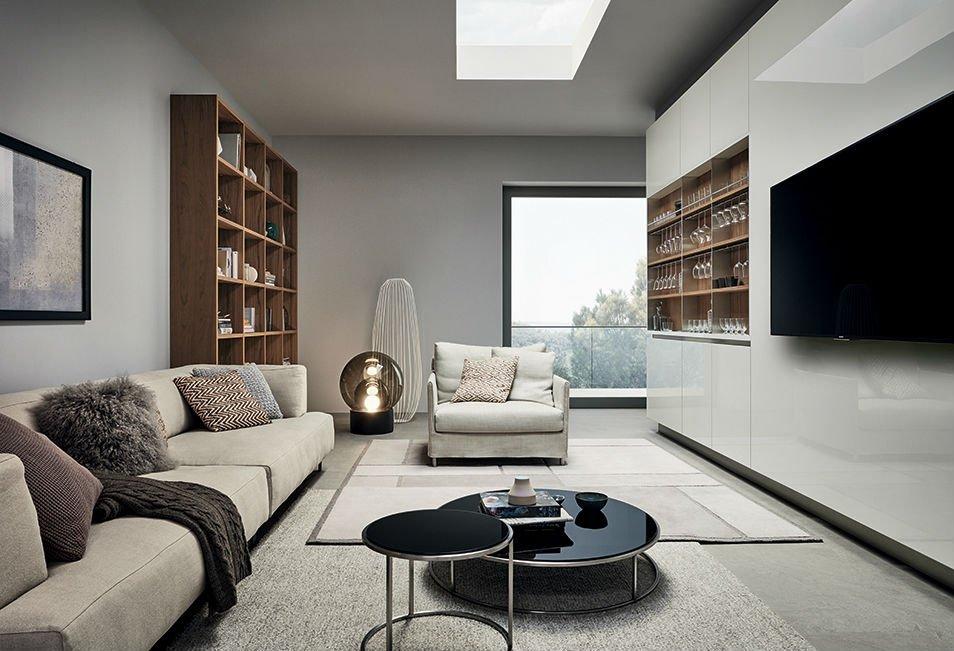 Sofà e poltrona di colore beige, scaffali con libri e altra scaffali piena di coppe, tavola bassa di duplice livello