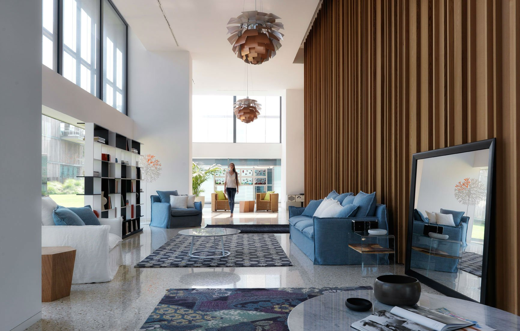 Grande salone con sofà, poltrone blu e bianca e scaffale nera e bianca