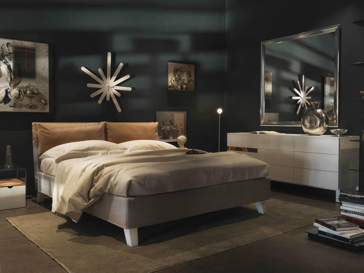 Camera da letto matrimoniale da toni bruni, orologio a forma di stella e originali tabelle