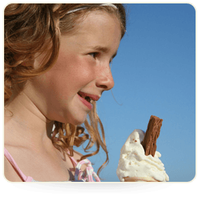 A young girl enjoying a a vanilla ice cream in a cone at the seaside