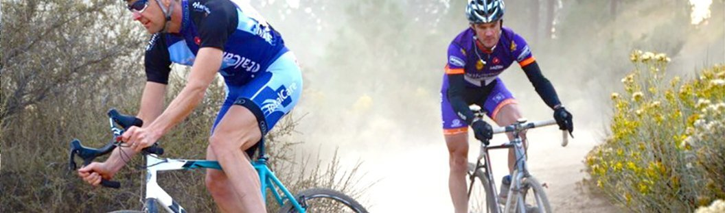 two cyclocross cyclists riding in a race