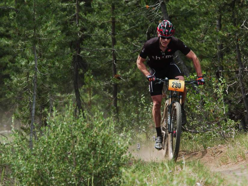 cyclist Adam Bucklin rides mountain bike up a hill