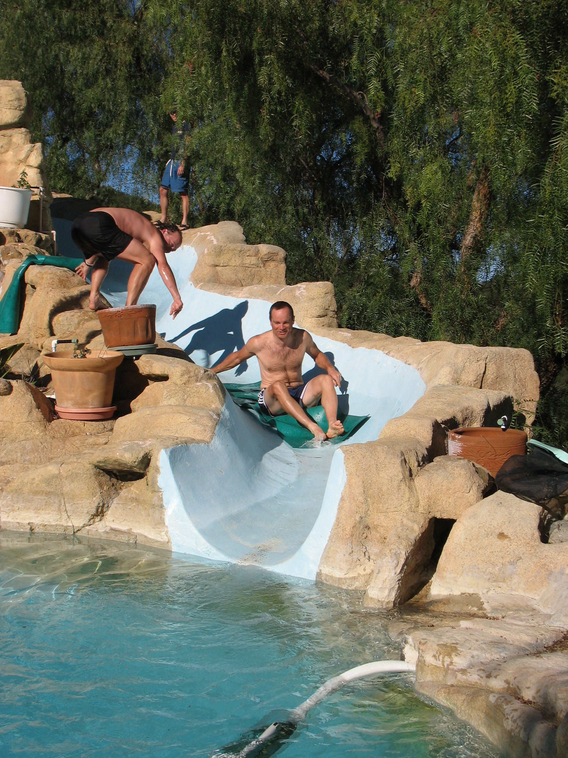Cyclists sliding down a water slide after a day of riding at cycling camp