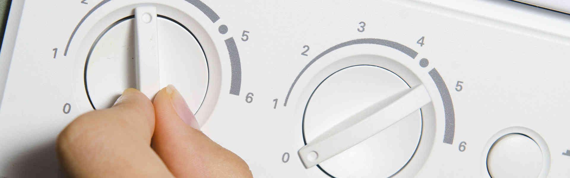mano umana con accensione caldaia a gas per il riscaldamento dell'acqua
