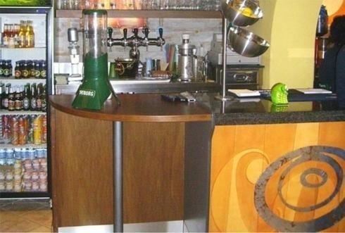vista frontale di un bancone di un bar con liquori e banco frigo