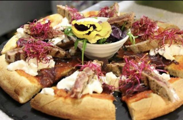una pizza con i filetti  di carne e dei petali