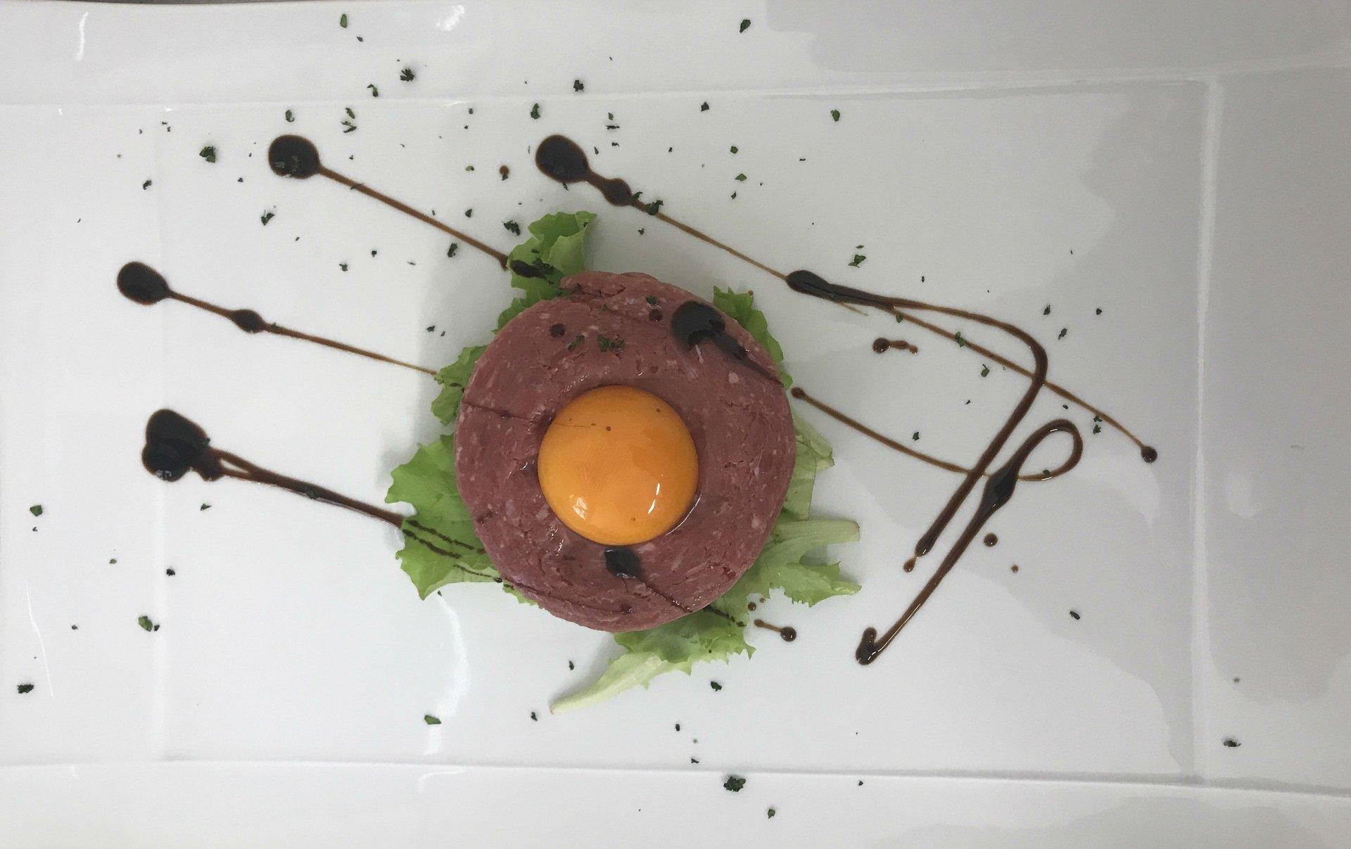 una tartare di carne con un tuorlo d'uovo sopra