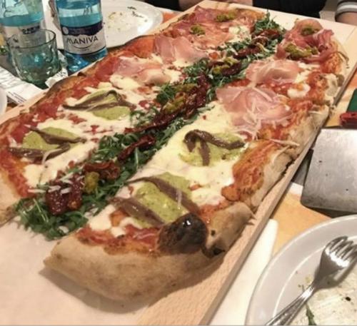 una pizza al metro tagliata in due e dell'insalata