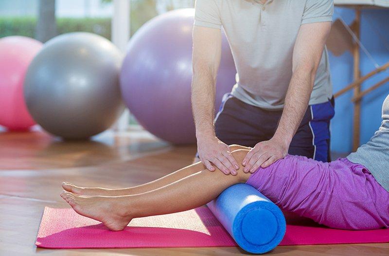 un massaggiatore che massaggia le ginocchia di una ragazza