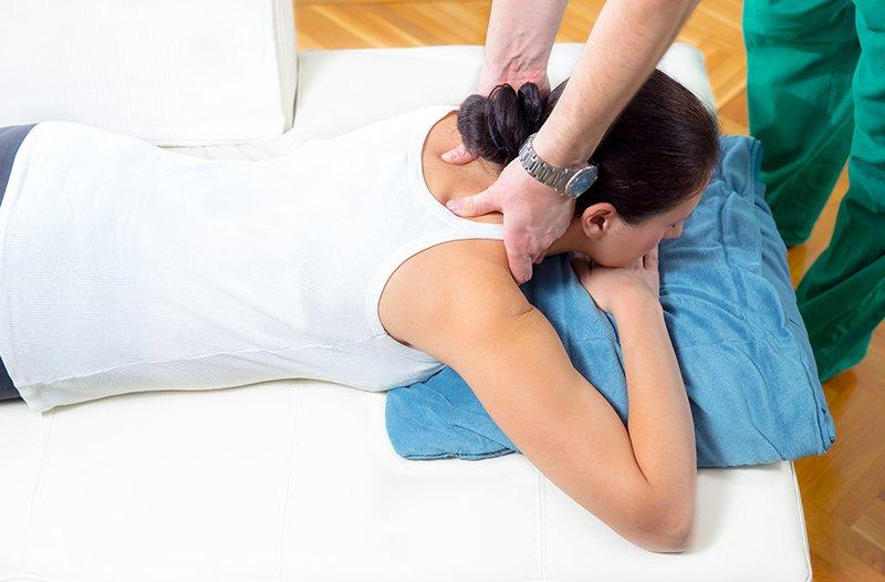un massaggiatore che massaggia il collo di una ragazza